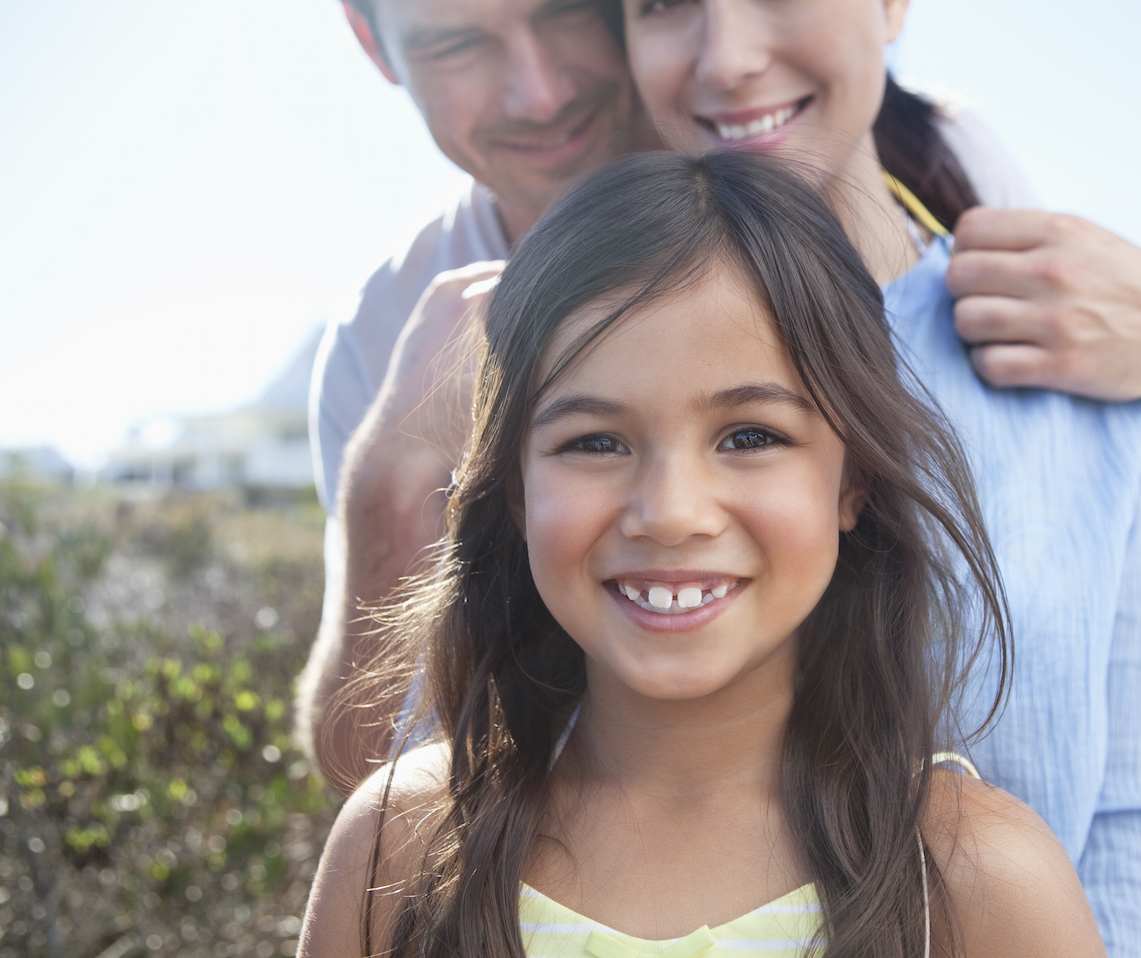Young smiling girl with her parents outside