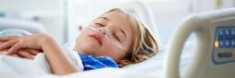 Young girl lies sleeping in hospital bed